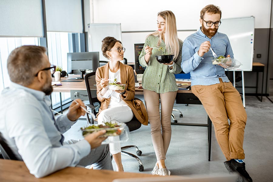 Life and Health Insurance - Coworkers in Business Casual Clothing Enjoy Salads and Perch on Desks and Chairs in Their Bright Open Office