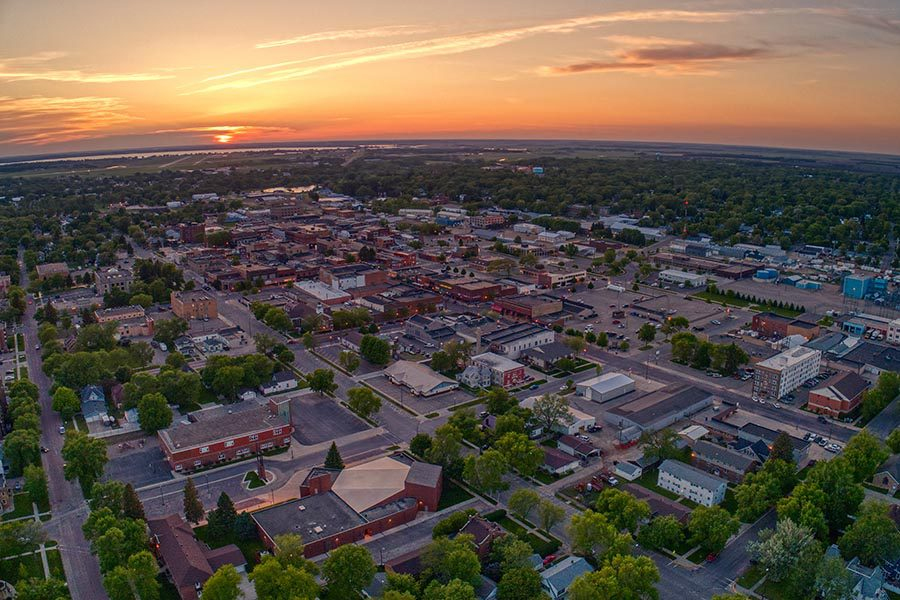 Watertown, SD Insurance - Aerial View of Watertown, SD With Buildings and Suburban Homes Lighting up at Sunset