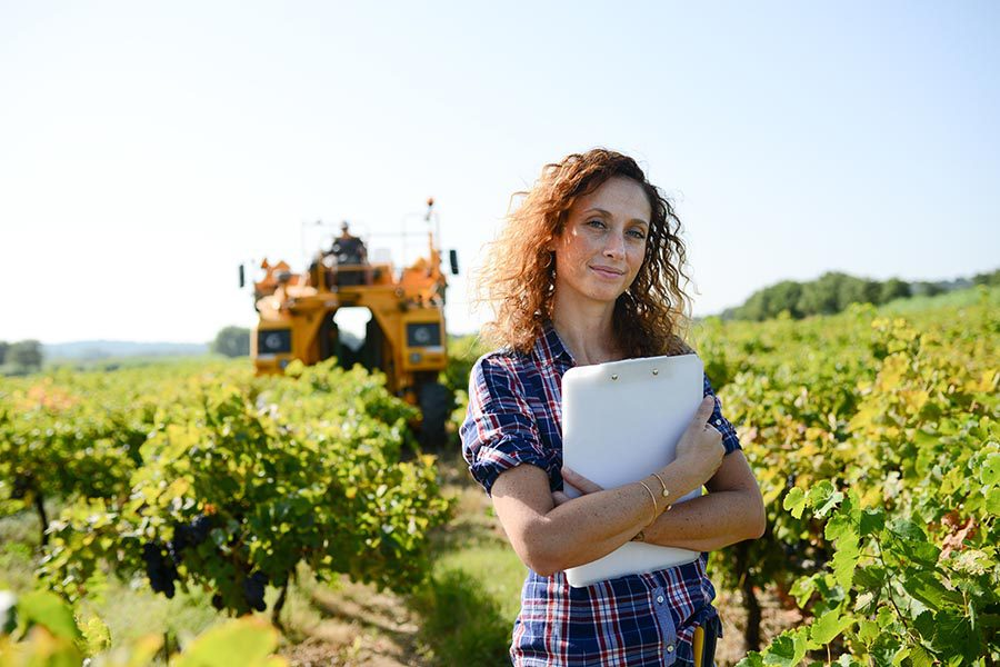 Specialized Business Insurance - Woman in Blue Flannel Shirt Holds Clipboard and Poses in Front of Field of Small Trees With Large Yellow Farm Equipment Behind Her