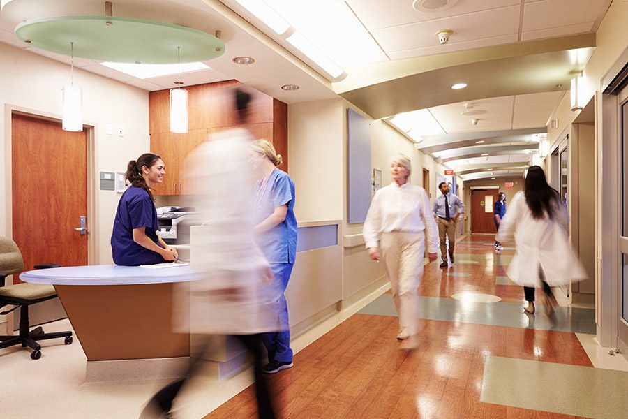 Group Hospital Insurance - Busy Group of Medical Professionals Busy Rushing Around the Hospital
