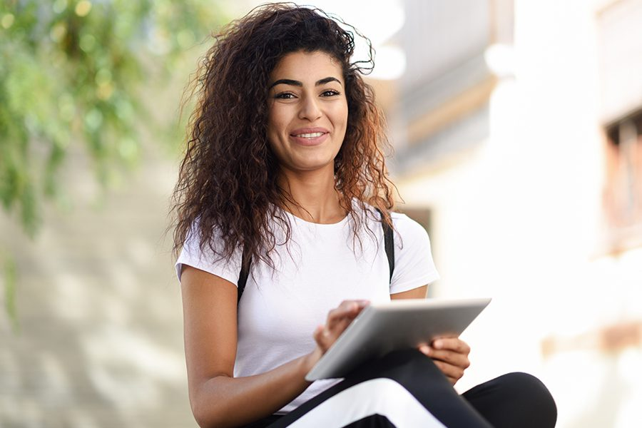 Client Center - Portrait of a Smiling Woman Using Tablet Outdoors on a Sunny Day