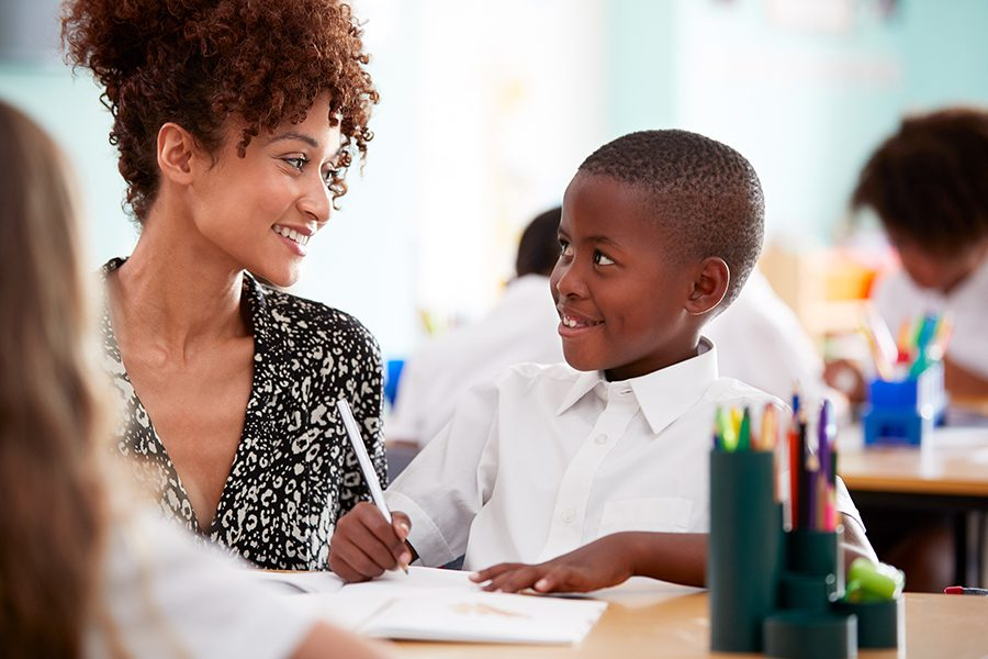 Interested Districts - Female High School Teacher Standing By Student Table Teaching Lesson