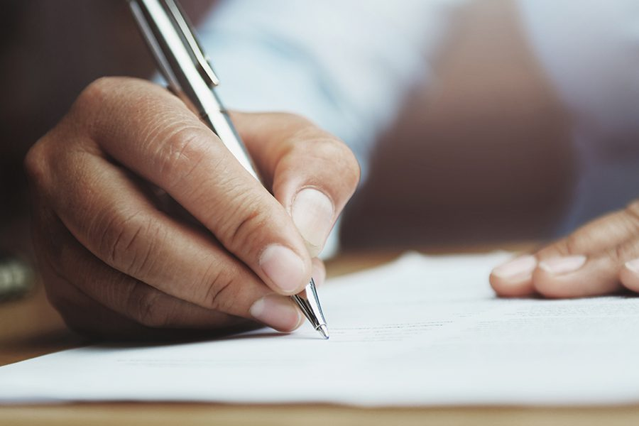 Payroll Administrators - Hand of Woman Holding Pen with Writing Administrative Tasks in Office