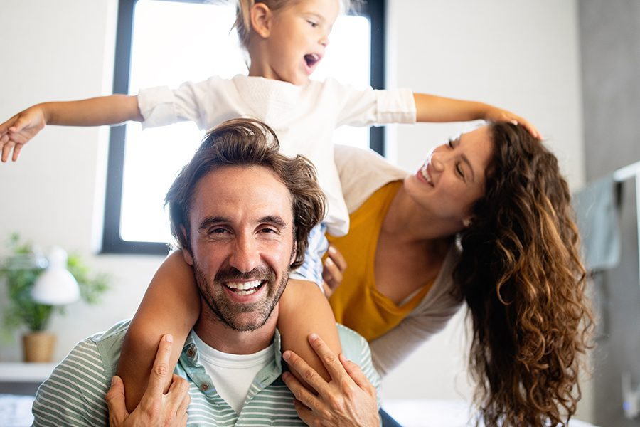 Personal Insurance - Happy Family Having Fun Time at Home With Young Girl on Her Father's Shoulders
