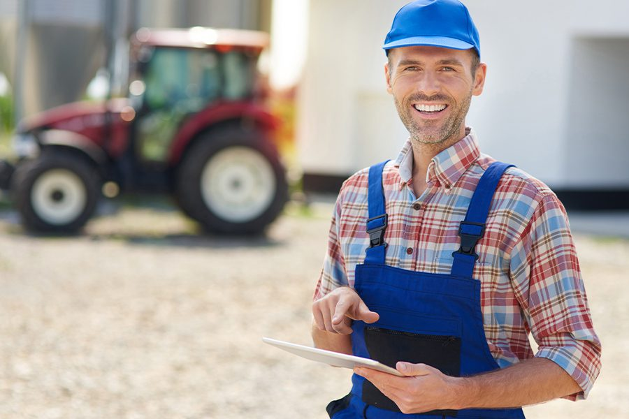Specialized Business Insurance - Young Farmer Using Tablet and Standing in Front of Tractor and Field Blurred in Distance on a Sunny Day