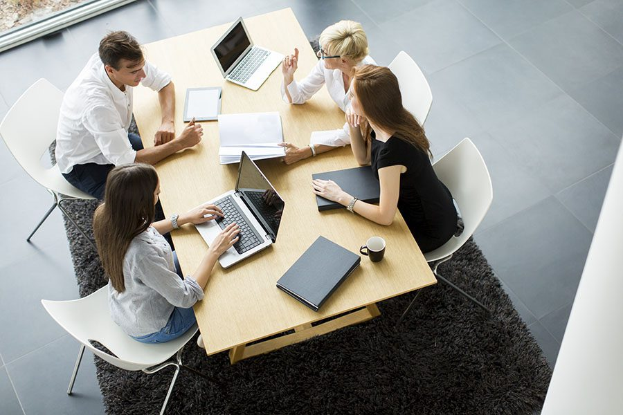 Contact - Group of Employees Sitting Around Table in the Office Working Together