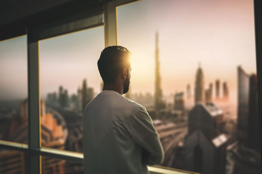 Insurance Quote - Man Standing in the Office Looking Out the Window at the View of the City