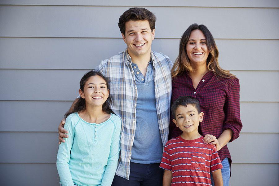 Personal Insurance - Portrait of Happy Family Standing in Front of Their House