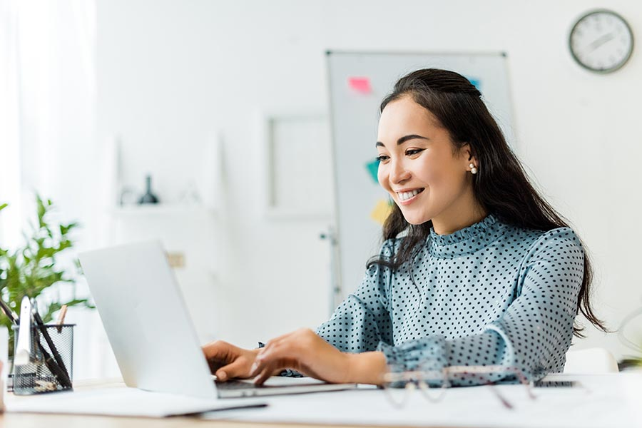 Blog - Young Woman in Polka Dot Blouse Smiles and Uses Her Laptop in a Bright White Office