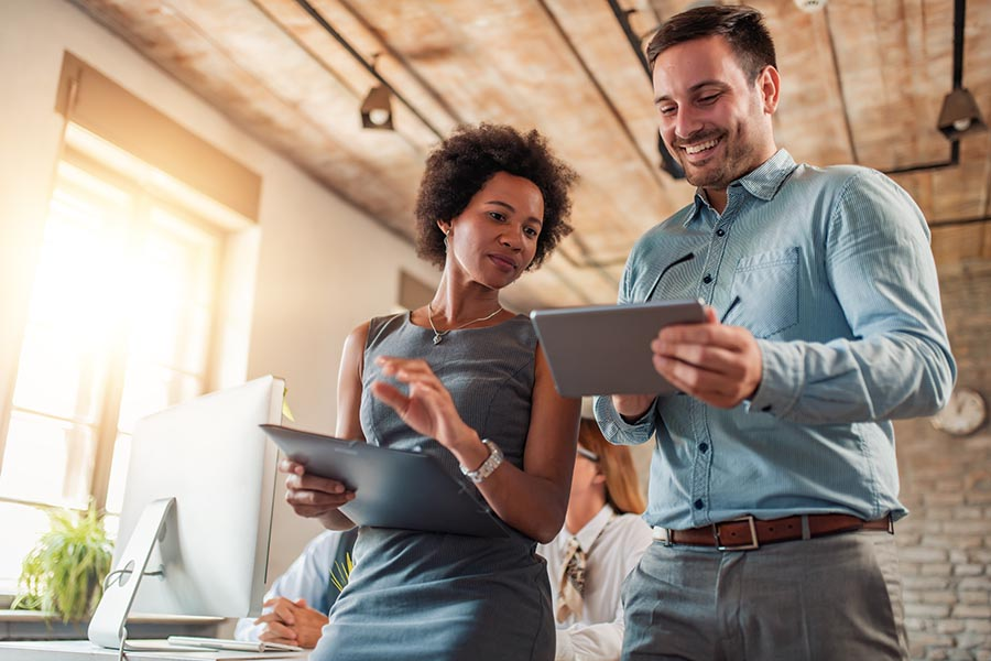 Business Insurance - Two Businesspeople Compare Notes Between Their Tablets and Smile, Standing in a Sunny Office With Employees Working Nearby