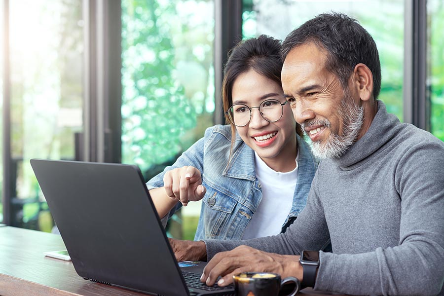 Client Center - Young Woman Helps Father Use Laptop in Their Home at a Wooden Table, Both Dressed Casually Any Sitting Close