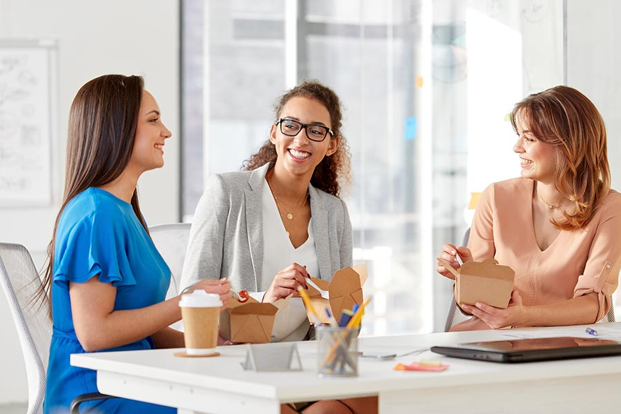 Employee Benefits - Three Professionally Dressed Coworkers Smile at a Communal Table as They Enjoy Lunch and Coffee