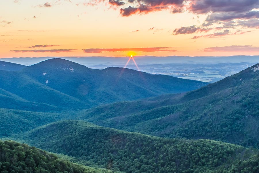 Harrisonburg, VA Insurance - the Tree-Covered Blue Ridge Mountains in Summer, With a Bright Sunset and the Sun Just Hitting the Horizon