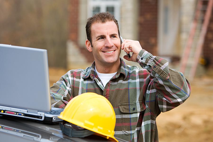 Specialized Business Insurance - Smiling Contractor Makes a Call With His Laptop and Hardhat Propped on Truck Hood, a Residential Job Site Behind Him