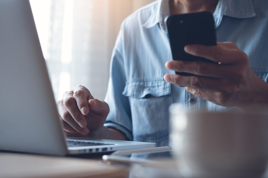 Blog - Closeup of Man Working on Laptop and using Phone from Home
