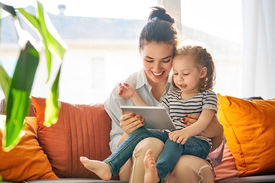 Client Center - Mom with Child in Her Lap Using a Tablet on the Sofa