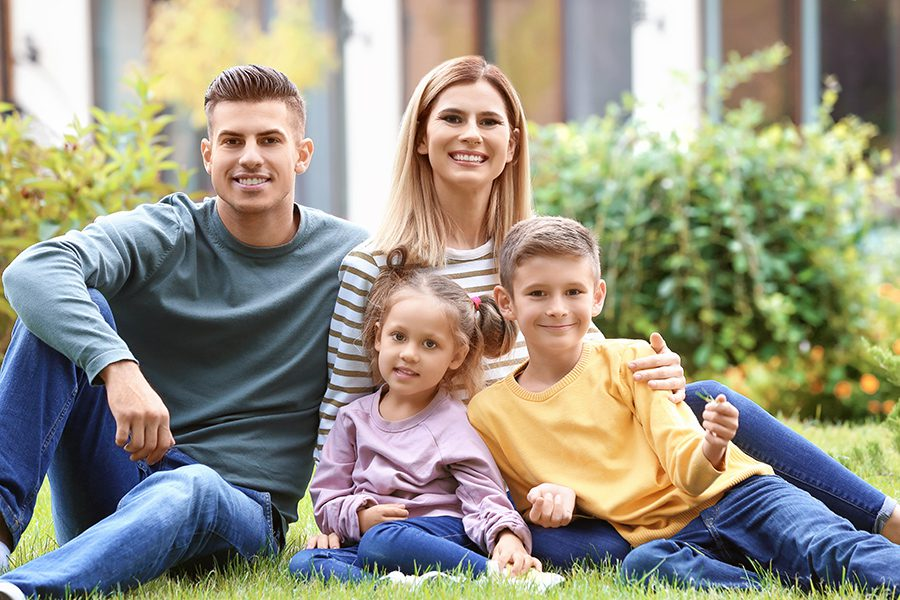 Personal Insurance - Happy Family Sitting on Grass in in Front of Their New House