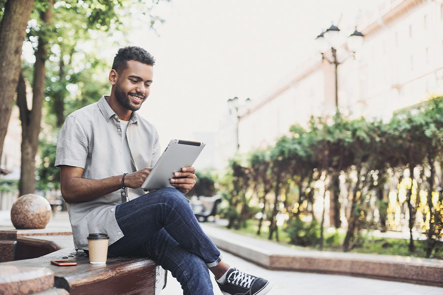Client Center - Smiling Young Man Using Tablet Outside in a City in Missouri