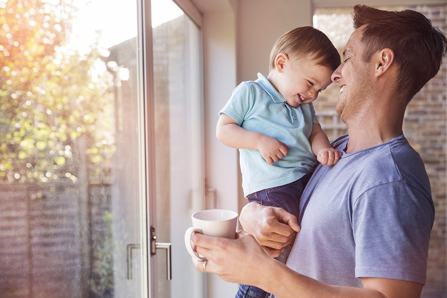 Personal Insurance - Happy Father Holds Toddler Son in Front of Patio Door While Drinking Coffee at Home