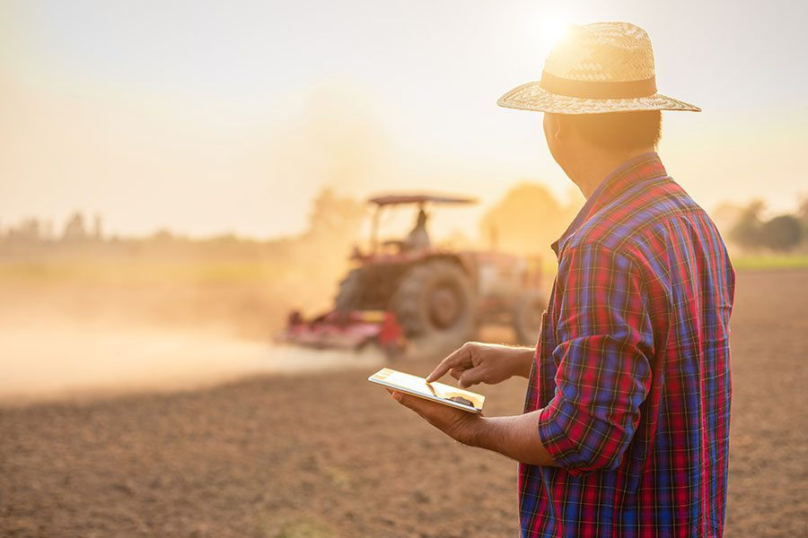 Contact - View of Farmer Holding a Tablet Standing in a Farm Field Lookign at Another Farmer Using the Tractor