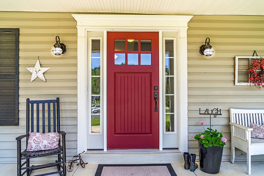 About Our Agency - View of the Front Porch of a Farmhouse with a Red Door and a Rocking Chair