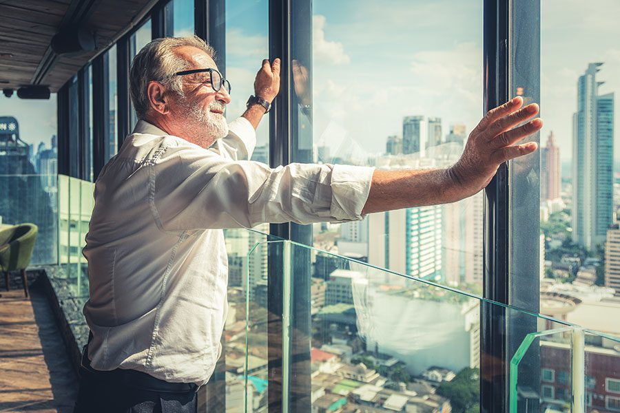 Business Insurance - View of a Mature Business Man Standing in His Office Looking Out the Glass Windows Out into the City