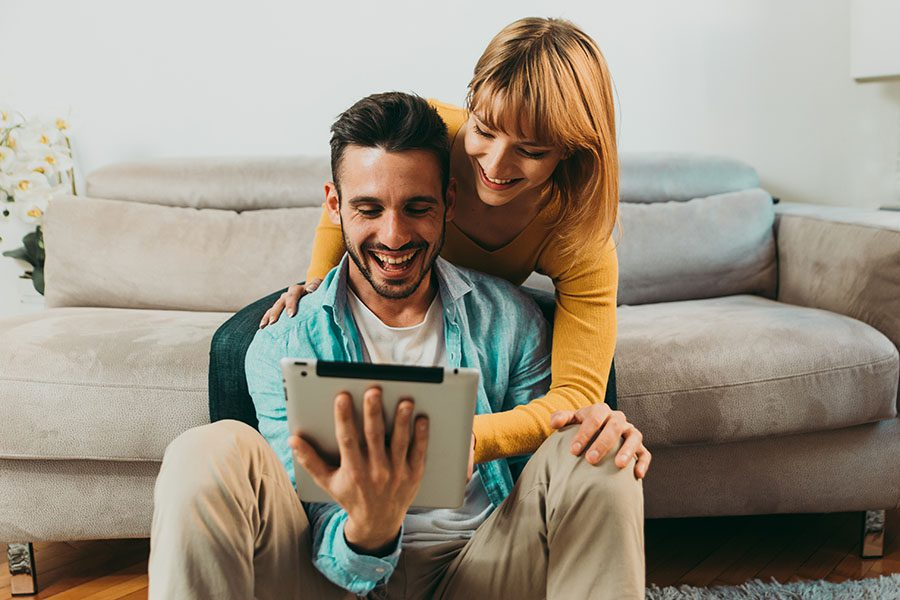 Client Center - Excited Young Couple Hanging Out in Their Living Room Using a Tablet