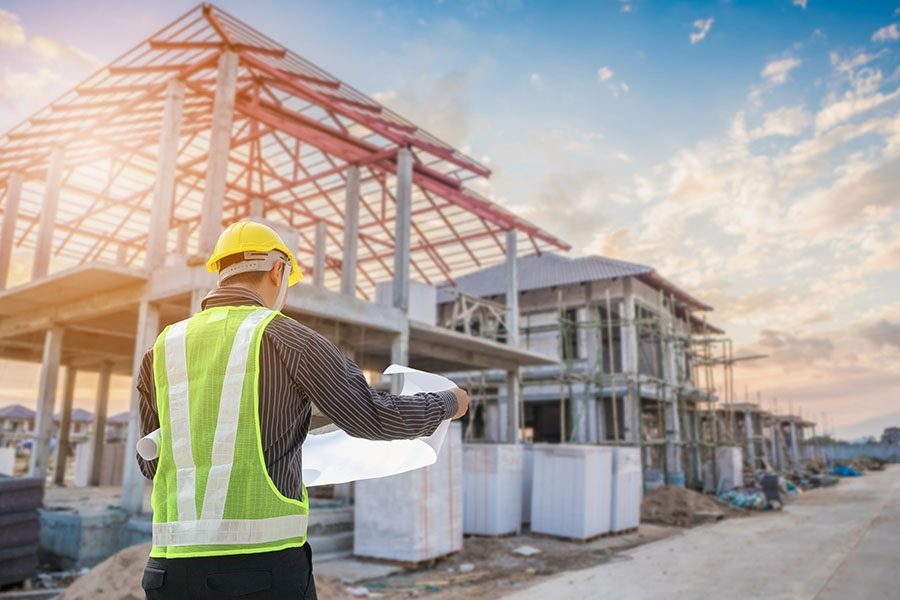 Specialized Business Insurance - Contractor Analyzing New Home Blueprints as He Stands on a Residential Construction Jobsite with a Partially Built Home