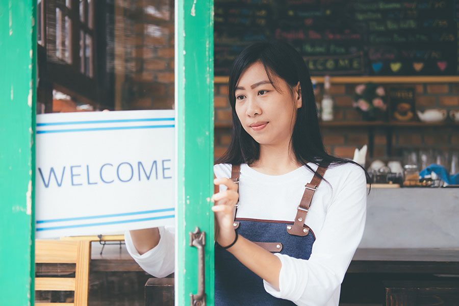 Business Insurance - View of Small Business Owner Putting Up Welcome Sign on Front Door