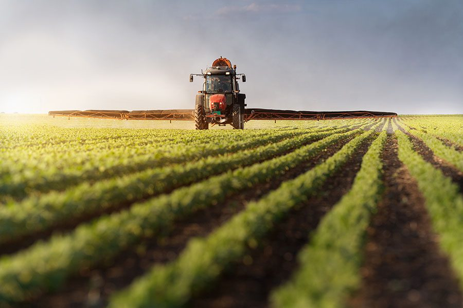 Specialized Business Insurance - View of Tractor Fertilizing Field of Crops on a Farm