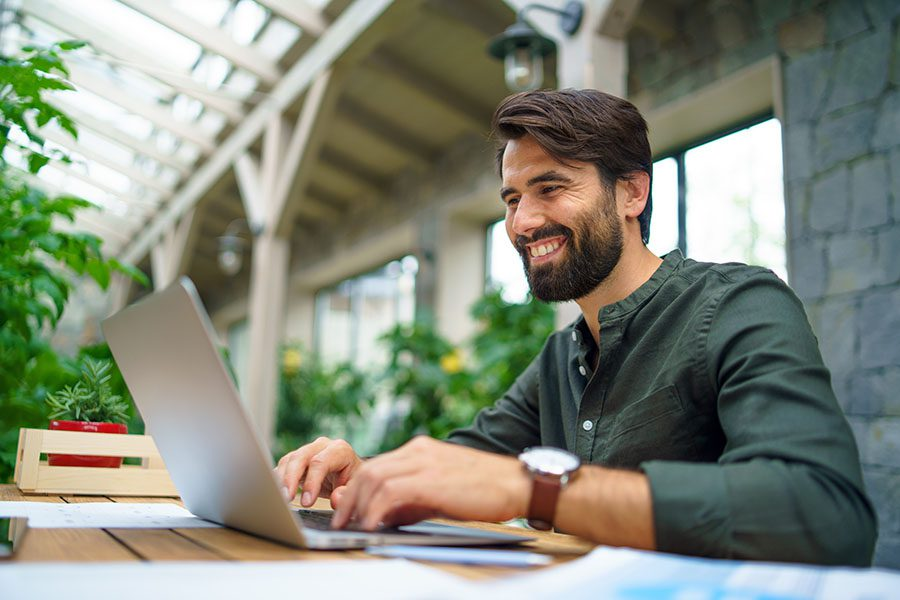 Blog - Portrait of Smiling Man Working on His Laptop in an Outdoor Workspace