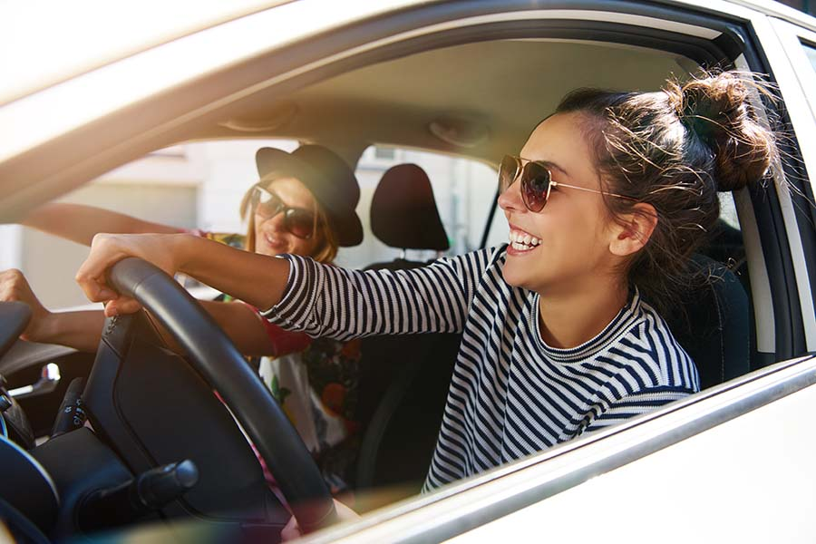 Insurance Quote - Smiling Woman Having Fun Driving in the Car with Her Friend on a Road Trip