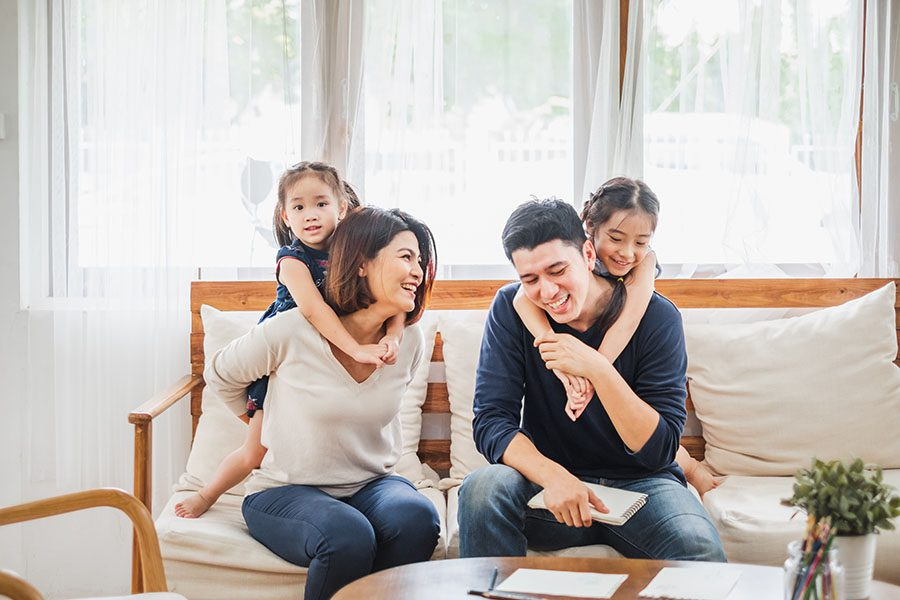 Personal Insurance - Cheerful Family Sitting in the Living Room with Their Two Kids