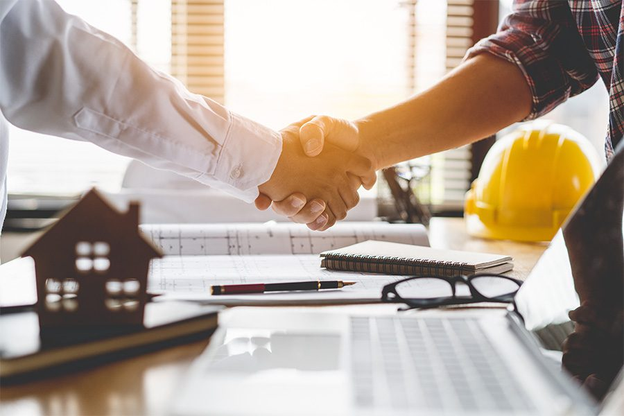 Specialized Business Insurance - Architect and Contractor Shaking Hands Over Table with New House Blueprints and Laptop