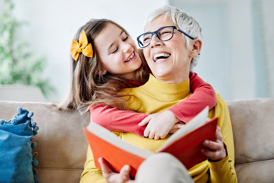 Blog - Grandmother and Granddaughter Having Fun in the Living Room on the Sofa with a Book