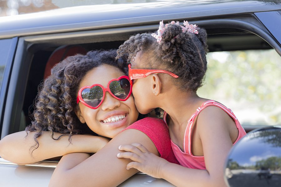 Personal Insurance - Happy Sisters with Heart Shaped Sunglasses in Car Ready for Summer