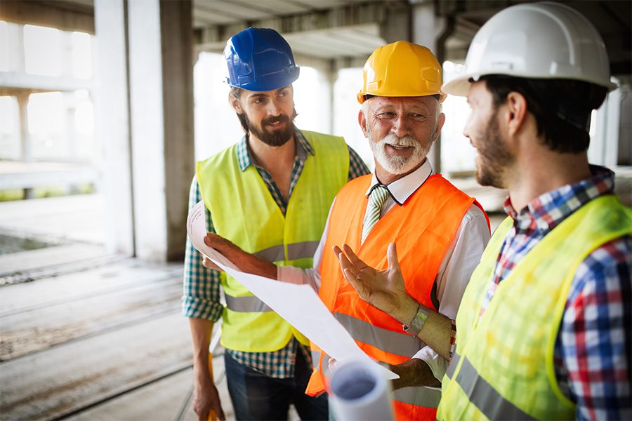 Specialized Business Insurance - Construction Engineers Discussing with Architects at Construction Building Site
