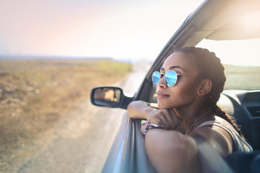 About Our Agency - Young Woman Looks Out the Window of a Car Driving Through the Southwest United States, the Blue Sky Reflected in Her Glasses