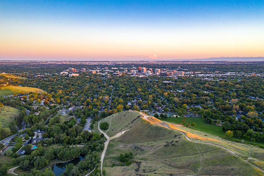 Boise, ID Insurance - Aerial Shot of Boise, Idaho From a Distance, With Green Hills in the Foreground and the Skyline Glowing Pink in the Sunset