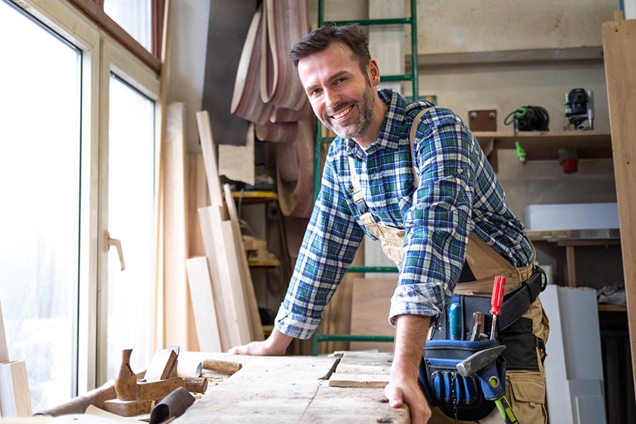 Business Insurance - Young Contractor Smiles Over His Workbench With Tools Surrounding Him, Wearing Blue Flannel and a Tool Belt