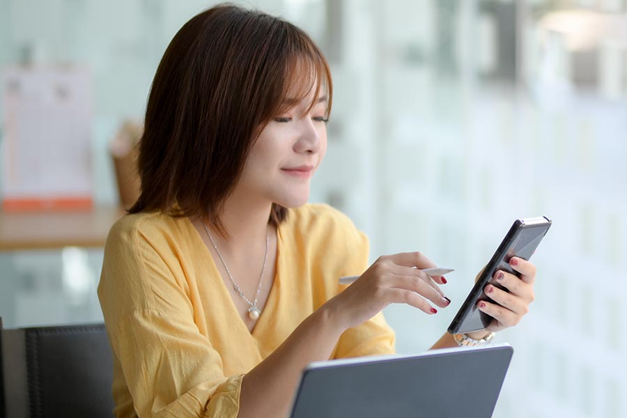 Client Center - Businesswoman Uses Her Phone and Laptop in Her Office, Wearing a Yellow Blouse