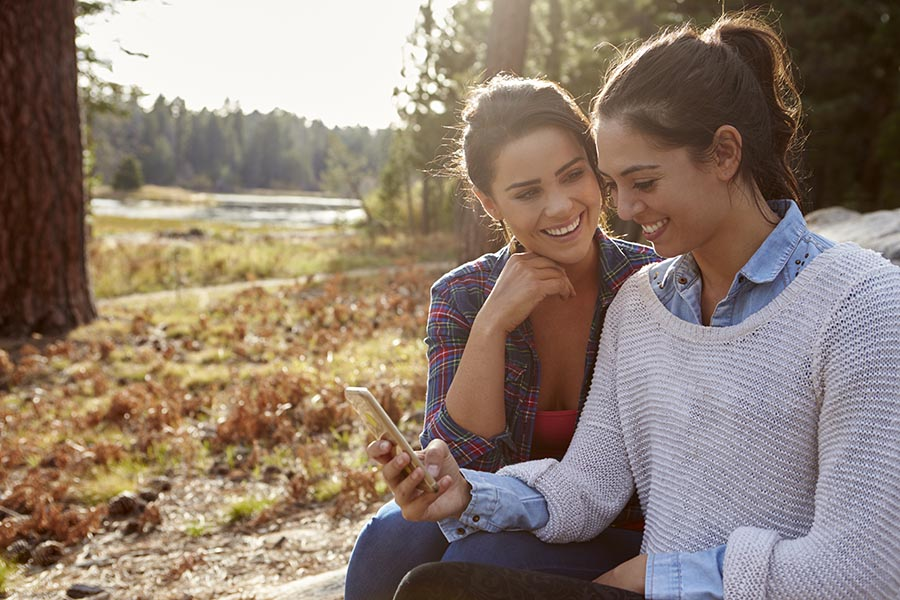 Contact Us - Couple in Fall Clothing Smiles and Uses Phone Seated by a Lake With Pine Trees Surrounding Them
