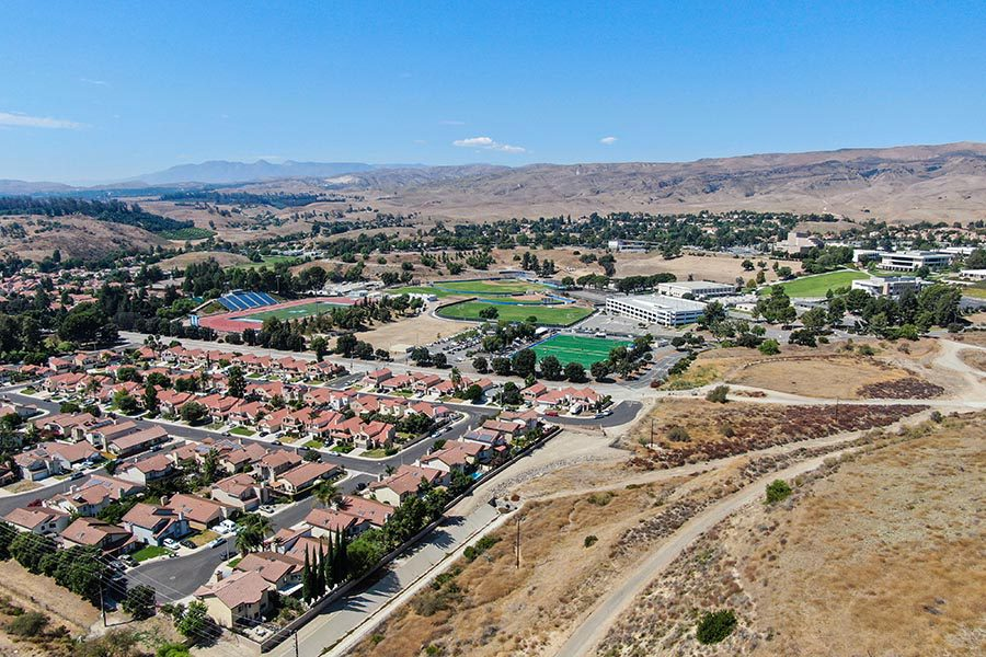 Moorpark, CA Insurance - Aerial Shot of Moorpark, California, With Hills, Suburban Neighborhoods, and Mountains in the Distance, Under a Bright Blue Sky