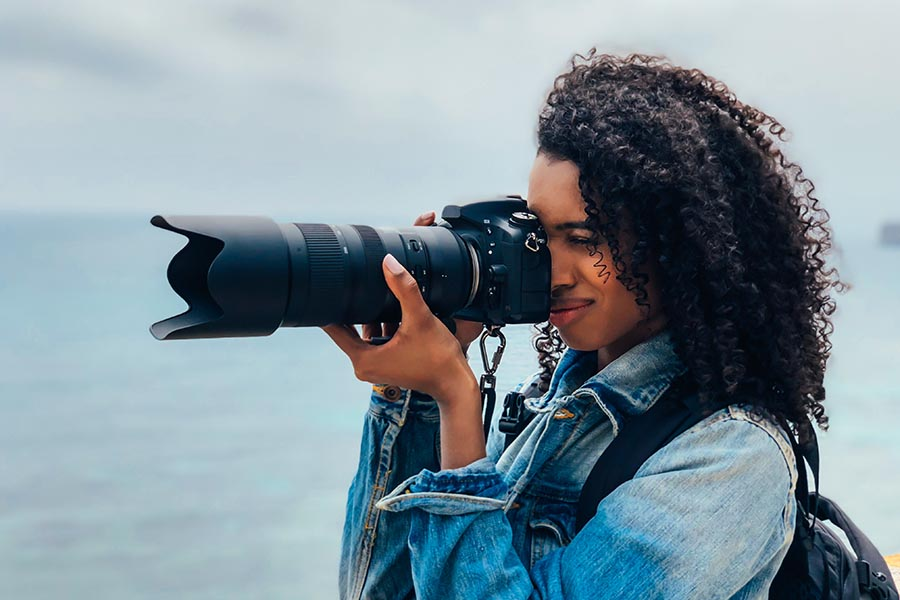 Specialized Business Insurance - Photographer Uses Large Professional Camera Standing by the Ocean Wearing a Jean Jacket