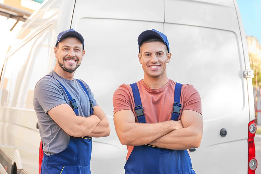 Business Insurance - Two Workers in Blue Overalls and Hats Stand in Front of Their Business's White Van and Smile