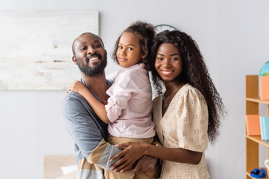 Personal Insurance - Family Hugs in Their Living Room, Young Daughter in Dad's Arms
