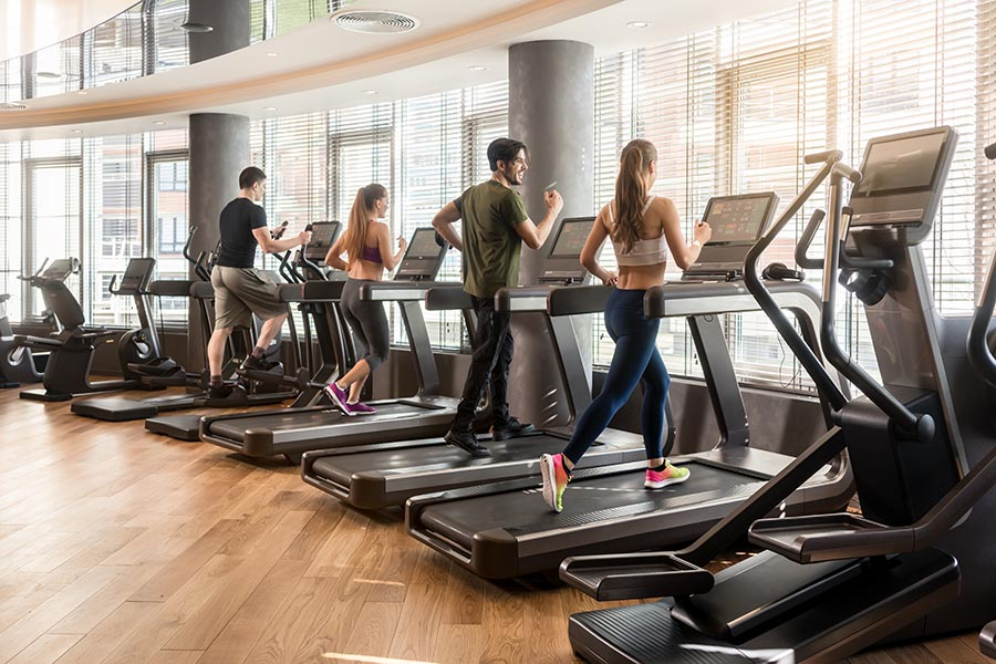 Specialized Business Insurance - Fitness Center With Several Members Running on Treadmills Facing a Large Curved Wall of Windows