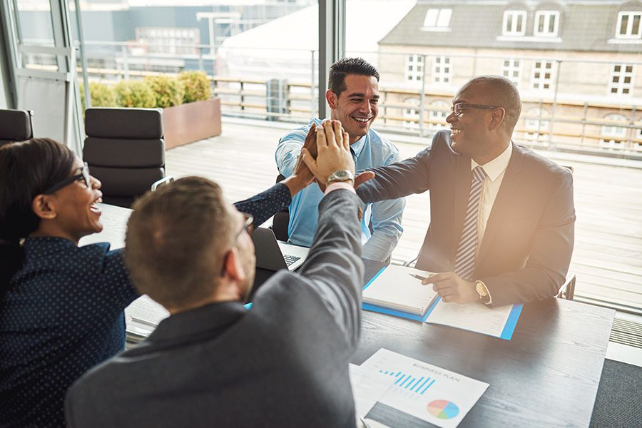 Business Insurance - Cheerful Group of Diverse Employees Sitting in a Business Meeting Giving Each Other High Fives