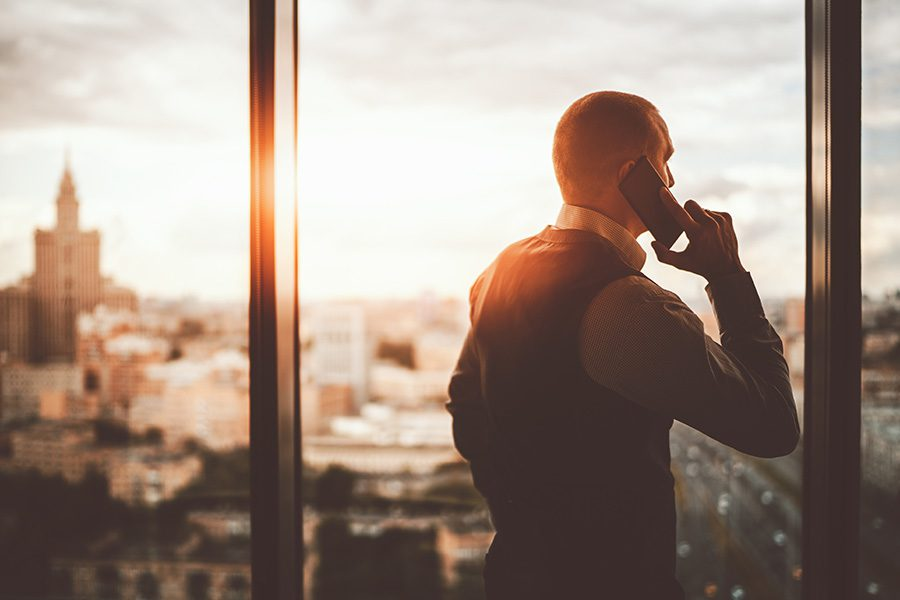 Contact - View of Businessman Talking on His Cellphone While Standing in His Office Looking Out Through the Window with Views of the City