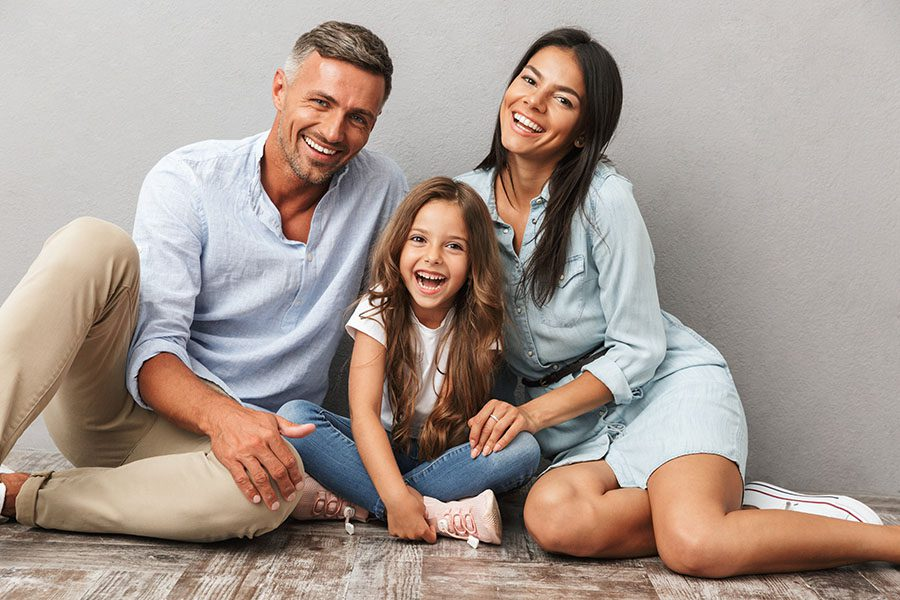 Personal Insurance - Portrait of Happy Family with Young Daughter Sitting on the Floor in Their Home